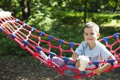 Мальчик в гамаке с бумажным стаканчиком питья стоковая фотография