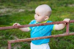 Мальчик в голубой рубашке льнет к железной загородке стоковое изображение