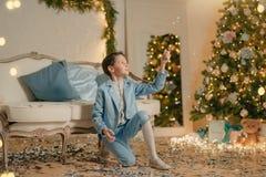 Мальчик в голубом костюме около рождественской елки стоковая фотография
