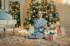 Мальчик в голубом костюме около рождественской елки стоковое изображение rf