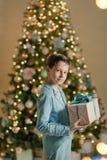 Мальчик в голубом костюме около рождественской елки стоковое изображение