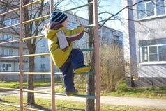 Мальчик, в детском саде, на спортивной площадке, взбирается на Sw Стоковые Изображения RF