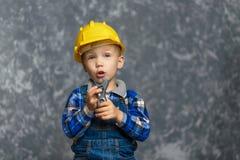 Мальчик в желтой трудной шляпе держа ключ для труб в руках Стоковое Изображение RF