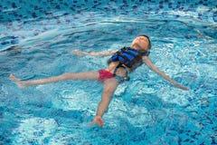 Мальчик в жилете на бассейна заплывания задней части дальше Детство, отдых, здоровый стоковые фото