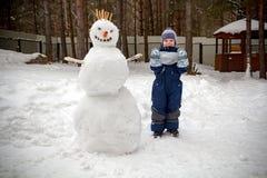 Мальчик в зиме в саде стоит рядом со снеговиком стоковая фотография