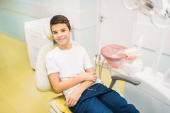 Мальчик в зубоврачебном стуле, педиатрическое зубоврачевание стоковое изображение