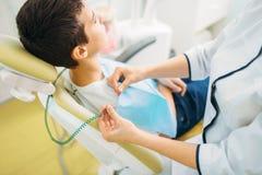 Мальчик в зубоврачебном стуле, педиатрическое зубоврачевание стоковые фотографии rf
