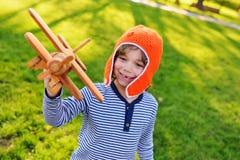 Мальчик в играть оранжевого шлема пилотный в плоскости игрушки деревянное против предпосылки травы Стоковые Фото