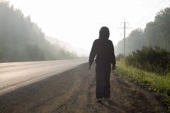 Мальчик в клобуке идет вдоль дороги Стоковое Изображение RF