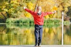 Мальчик в красной куртке стоя на доке с листьями в его руке Стоковое фото RF