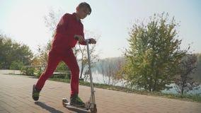 Мальчик в красной одежде едет скутер в парке Ребенк активно тратит время outdoors движение медленное сток-видео