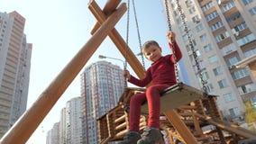 Мальчик в красном костюме отбрасывая на деревянном качании Счастливая концепция детства Предпосылка детского сада Здравоохранение сток-видео