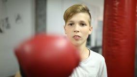 Мальчик в красных ударах кладя в коробку перчаток сток-видео