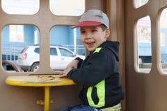 Мальчик в крышке играет с песком в деревянном доме Стоковые Фотографии RF
