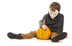 Мальчик в маске делая тыкву хеллоуина Стоковые Изображения
