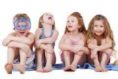 Мальчик в маске подныривания и 3 девушки сидят на полотенце стоковые изображения rf