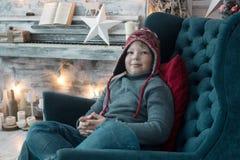 Мальчик в одеждах зимы в стуле на holyday предпосылке стоковая фотография