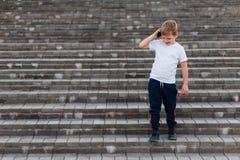 Мальчик в одеждах спорт вниз с лестниц и говорить по телефону outdoors стоковые фото