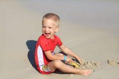 Мальчик в одеждах с УЛЬТРАФИОЛЕТОВЫМ фильтром играет с песком на пляже морем, праздником с детьми, защищая детей от стоковая фотография rf