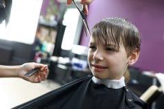 Мальчик в парикмахерскае Стоковая Фотография