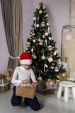 Мальчик в подарках рождества отверстия шляпы Санты красных Стоковые Фото