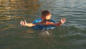 Мальчик в раздувном круге потехи в море видеоматериал