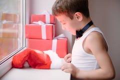 Мальчик в рубашке и бабочке связи смотрит подарки шляпы Санты Стоковая Фотография RF