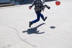 Мальчик в скачке, ребенок бежать после шарика играя футбол на асфальте, скачку шарика, игрока футбольной команды, тренировку внеш Стоковая Фотография