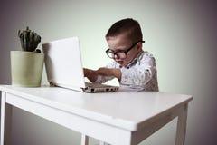 Мальчик в стеклах сидящ и работающ за компьтер-книжкой стоковое изображение