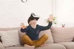 Мальчик в шлемофоне виртуальной реальности играя видеоигру дома стоковые фотографии rf