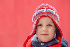 Мальчик в шляпе зимы представляет перед красной предпосылкой стоковые фото