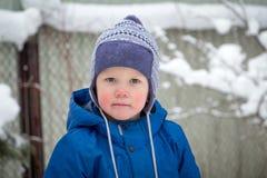 Мальчик в шляпе и куртке зимы пока идущ на день холодной зимы снежный стоковое изображение