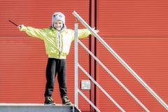Мальчик в шляпе усмехается и распространил его руки в различных направлениях, играя в дворе города Утеха ` s детей и концепция св Стоковое Фото