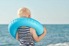 Мальчик в striped футболке и кольце жизни вокруг его шеи стоящ и смотрящ море Стоковое фото RF