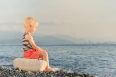 Мальчик в striped футболке сидя на пляже с ручкой Море, горы и город с небоскребами в расстоянии против bac Стоковые Фото