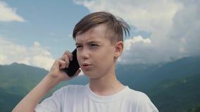 Мальчик говоря на смартфоне пока путешествующ против фона высоких гор акции видеоматериалы