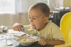 Мальчик 2 года ест кашу Children& x27; таблица s Концепция child& x27; независимость s счастливая еда мальчика стоковое фото rf