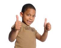 мальчик давая большие пальцы руки поднимает детенышей стоковое фото rf