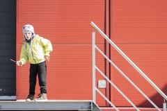 Мальчик двигает как робот мальчик играет в территории промышленного предприятия против предпосылки стены профиля металла Портрет  стоковые фотографии rf