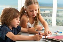 Мальчик девушки помогая с домашней работой. Стоковая Фотография RF
