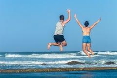 Мальчик девушки скачет бассейн океана пляжа перескакивания приливный Стоковые Фотографии RF