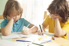 Мальчик 2 делает его домашнюю работу для начальной школы Стоковые Фотографии RF