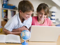 мальчик делающ компьтер-книжку домашней работы девушки их Стоковая Фотография