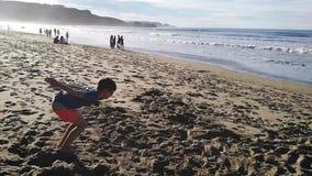 Мальчик делая большой скачок на пляже сток-видео