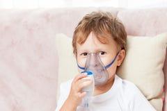 Мальчик делая вдыхание с nebulizer дома стоковые фотографии rf