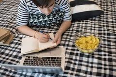 Мальчик делая домашнюю работу на кровати Стоковая Фотография RF