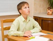 мальчик делая его детенышей домашней работы думая Стоковая Фотография