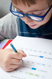 мальчик делая элементарную домашнюю работу Стоковая Фотография