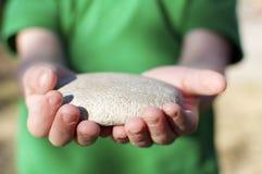 мальчик держа меньший камень Стоковые Фотографии RF