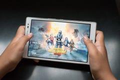Мальчик держа цифровую таблетку играя онлайн передвижную игру вызвал PUBG стоковое изображение